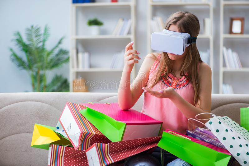 A jovem mulher que faz a compra com vidros da realidade virtual fotos de stock