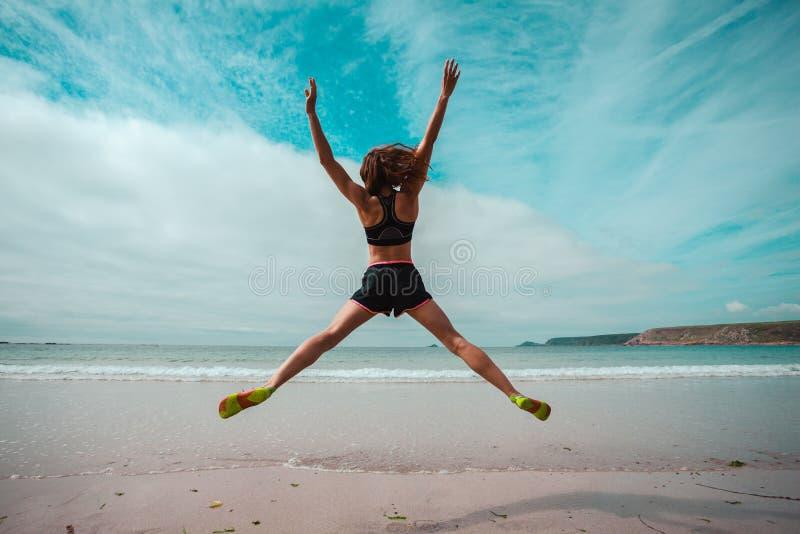 A jovem mulher que faz a estrela salta na praia imagens de stock royalty free