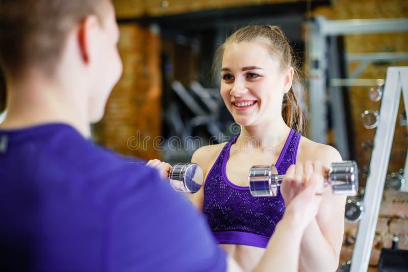 Jovem mulher que faz exercícios com pesos no gym com um instrutor pessoal fotografia de stock