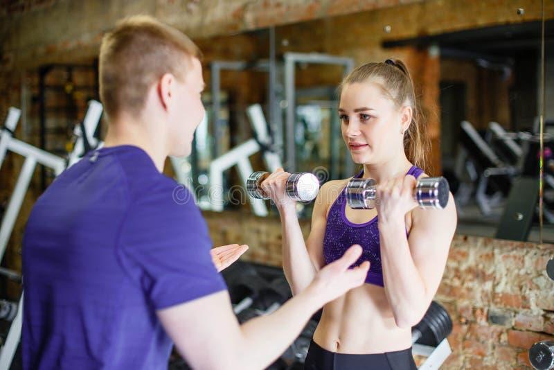 Jovem mulher que faz exercícios com pesos no gym com um instrutor pessoal fotos de stock