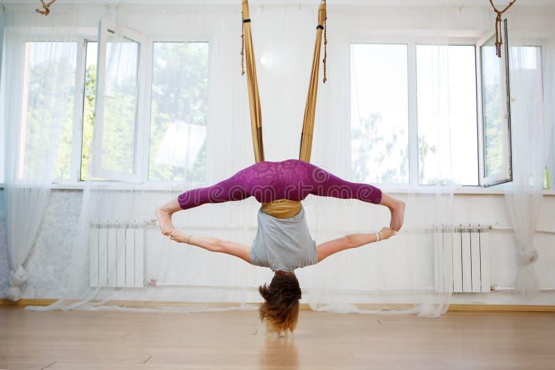 Jovem mulher que faz exercícios da ioga aérea na rede imagens de stock royalty free