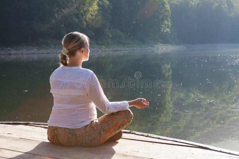 Jovem mulher que faz exercícios da ioga no lago imagens de stock royalty free