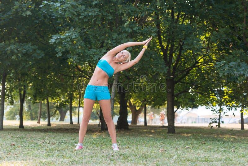 Jovem mulher que faz exercícios dos esportes no parque foto de stock royalty free