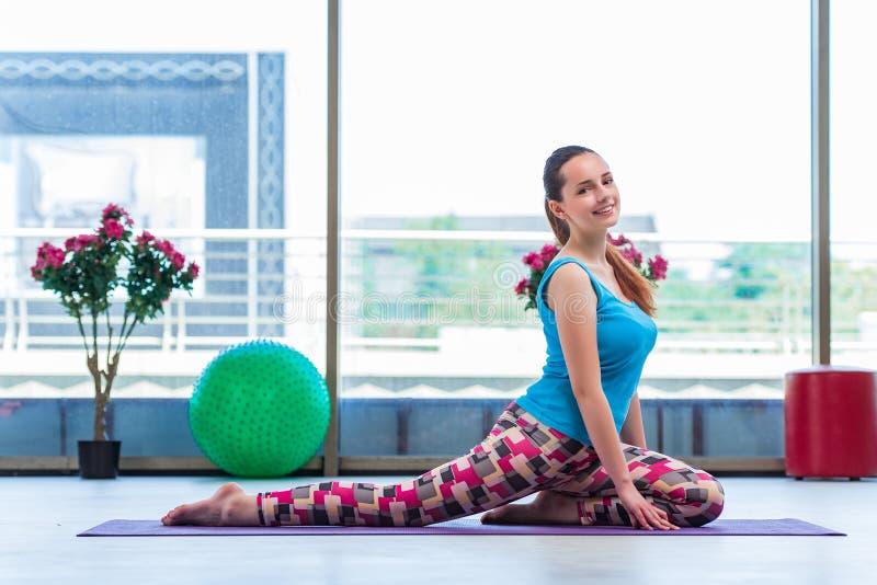 A jovem mulher que faz exercícios no conceito da saúde do gym fotos de stock royalty free