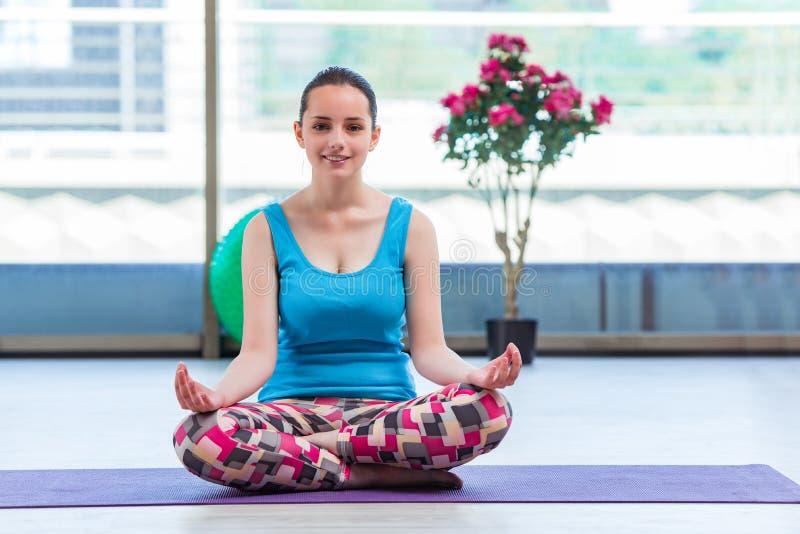 A jovem mulher que faz exercícios no conceito da saúde do gym imagem de stock