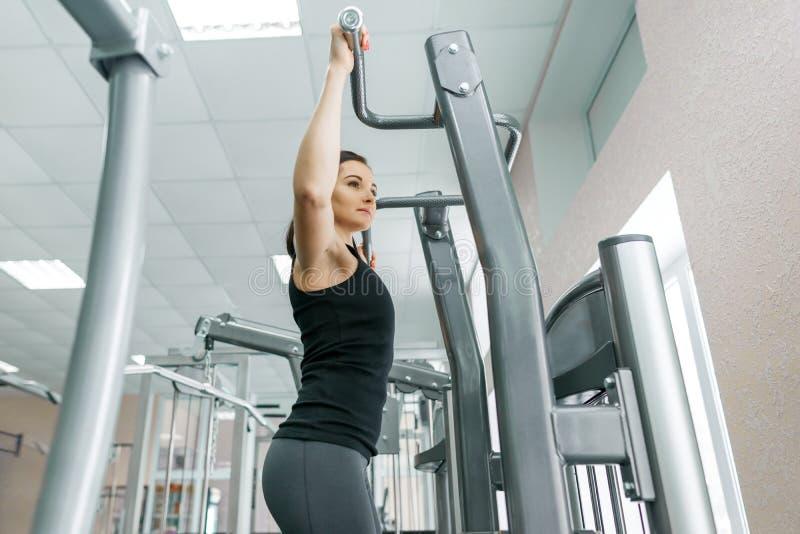 Jovem mulher que faz exercícios para a parte traseira em uma máquina da aptidão no gym Aptidão, esporte, treinamento, conceito do fotografia de stock