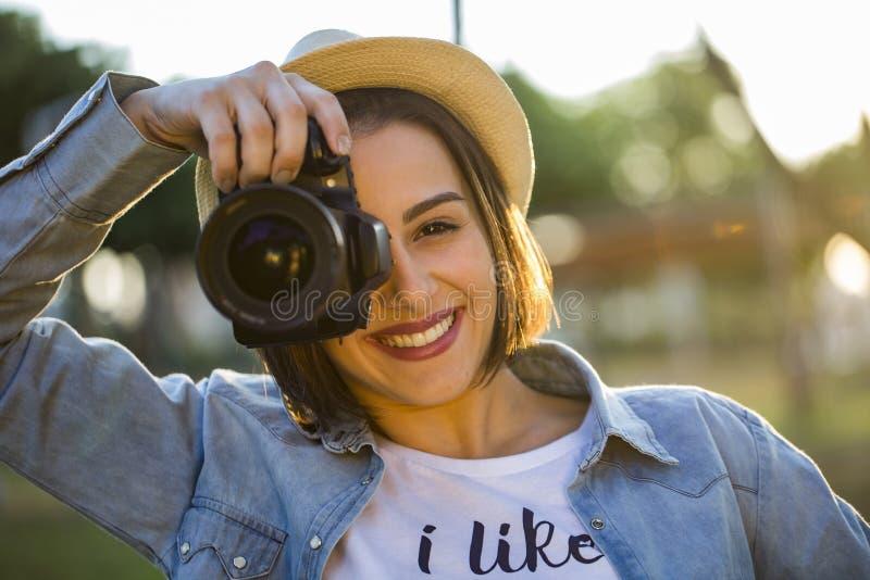Jovem mulher que faz fotos com a câmera profissional no gre do verão fotografia de stock