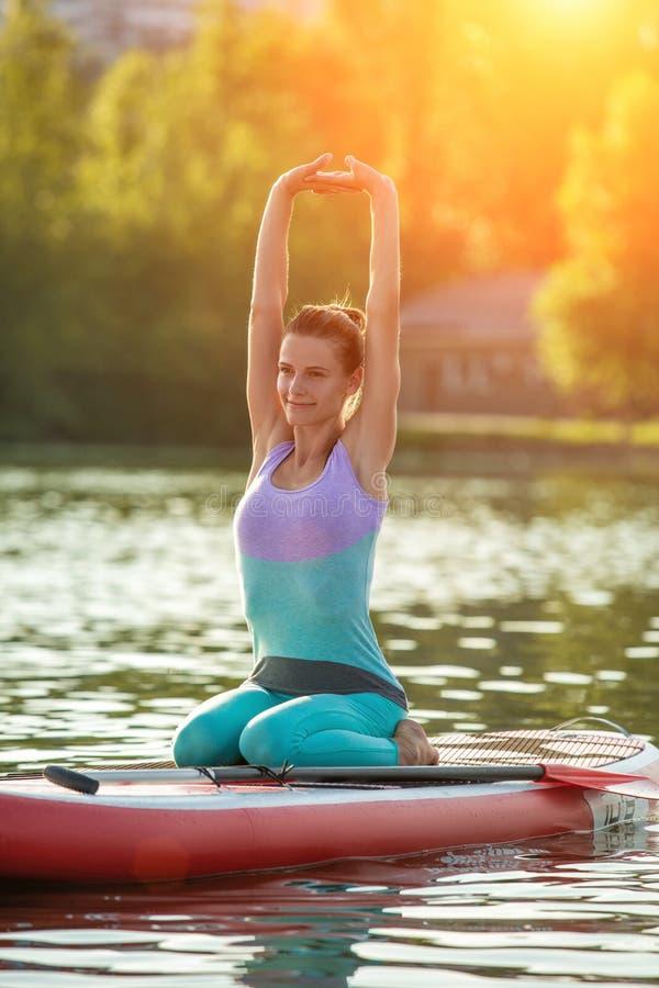Jovem mulher que faz a ioga na placa do sup com pá Pose da ioga, vista lateral - conceito da harmonia com a natureza fotografia de stock royalty free