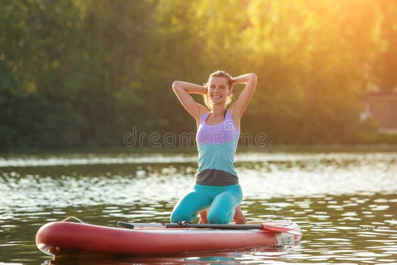 Jovem mulher que faz a ioga na placa do sup com pá Pose da ioga, vista lateral - conceito da harmonia com a natureza foto de stock royalty free