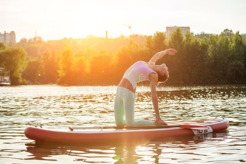 Jovem mulher que faz a ioga na placa do sup com pá Pose da ioga, vista lateral - conceito da harmonia com a natureza imagem de stock