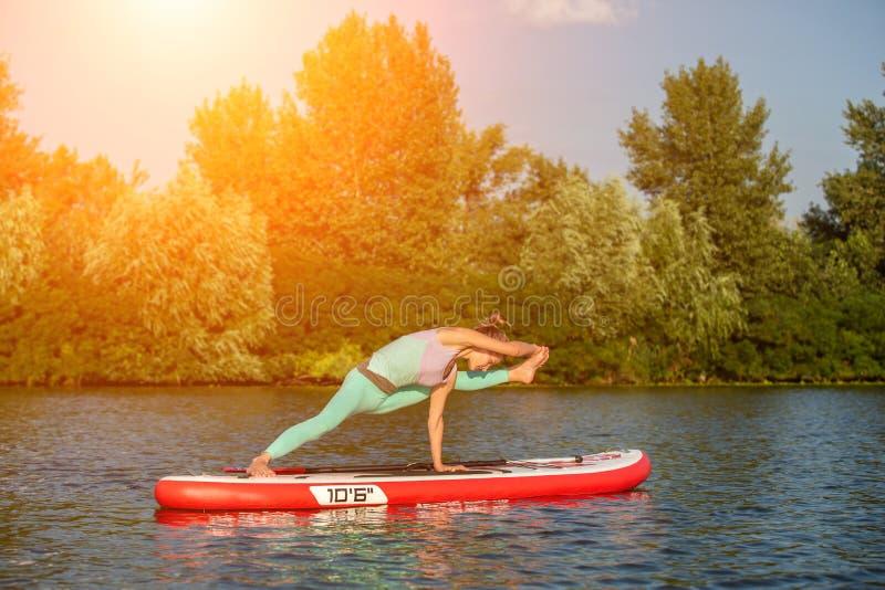 Jovem mulher que faz a ioga na placa do sup com pá Pose da ioga, vista lateral - conceito da harmonia com a natureza fotos de stock royalty free