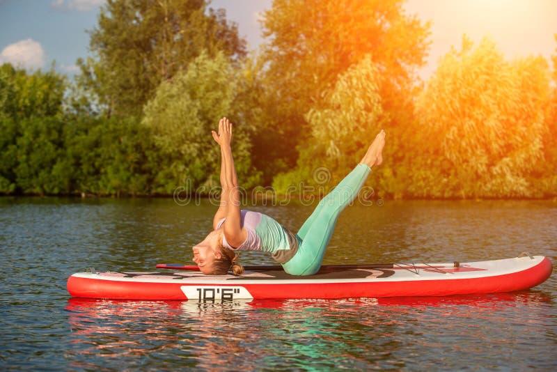 Jovem mulher que faz a ioga na placa do sup com pá Pose da ioga, vista lateral - conceito da harmonia com a natureza foto de stock