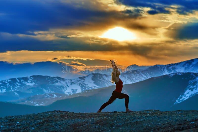 Jovem mulher que faz a ioga nas montanhas fotografia de stock