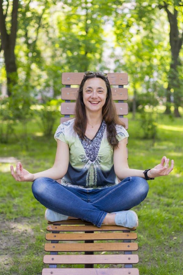 Jovem mulher que faz a ioga no parque no banco Retrato da mulher moreno nova bonita calma que relaxa e que faz o exerc?cio da iog imagem de stock