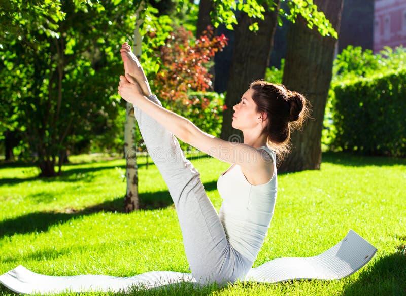 Jovem mulher que faz a ioga no parque na manhã imagem de stock