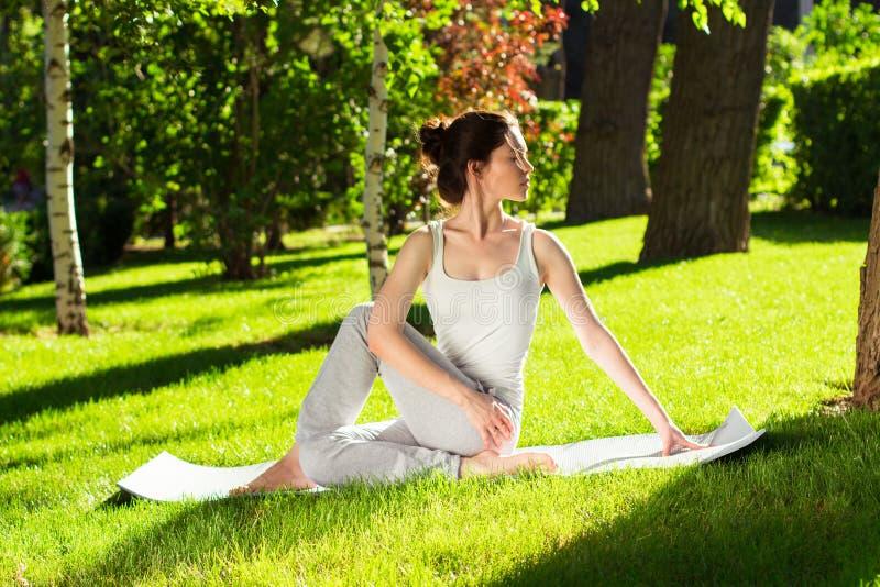 Jovem mulher que faz a ioga no parque na manhã foto de stock royalty free