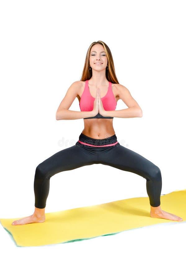 Jovem mulher que faz a ioga no tiro do estúdio da esteira fotografia de stock