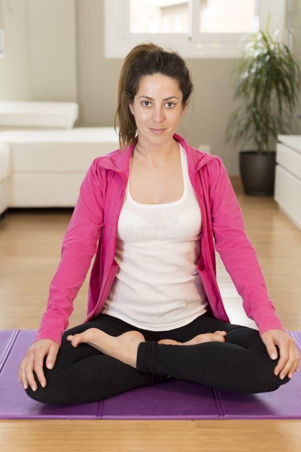 Jovem mulher que faz a ioga que estica o exercício fotografia de stock royalty free
