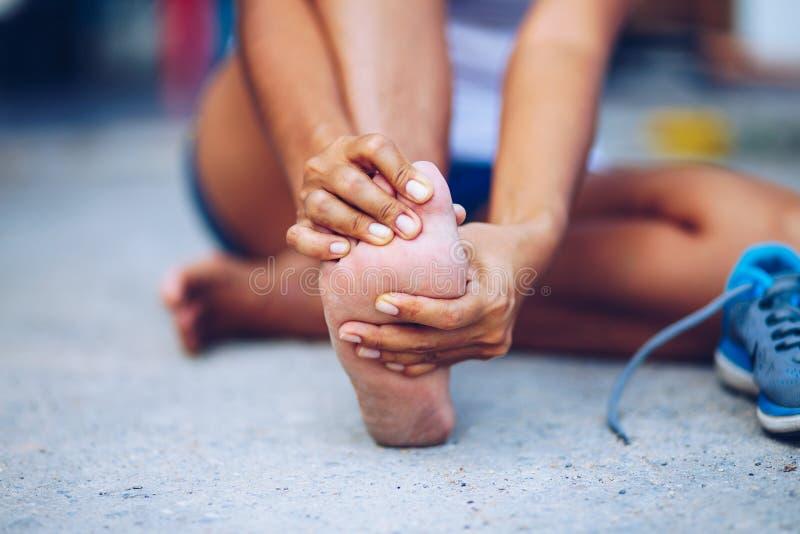 Jovem mulher que faz massagens seu pé doloroso do exercício fotos de stock