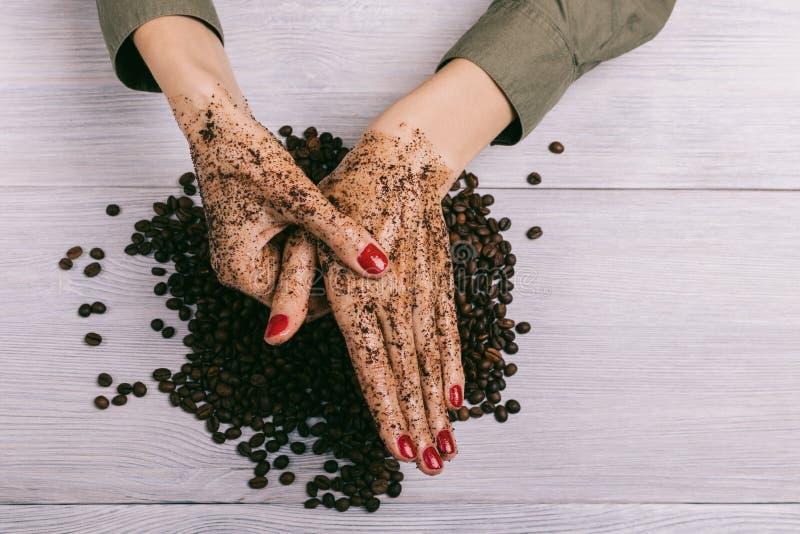A jovem mulher que faz massagens uma mão com café esfrega imagens de stock