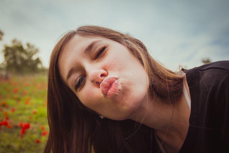 Jovem mulher que faz o beijo do duckface ao tomar a imagem do selfie com seu smartphone ou a câmera no campo de papoilas vermelha fotos de stock