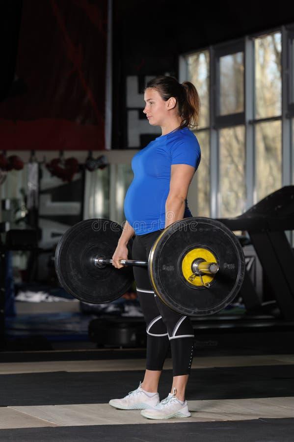 Jovem mulher que faz o deadlift para malhar com o barbell pesado no gym escuro foto de stock royalty free