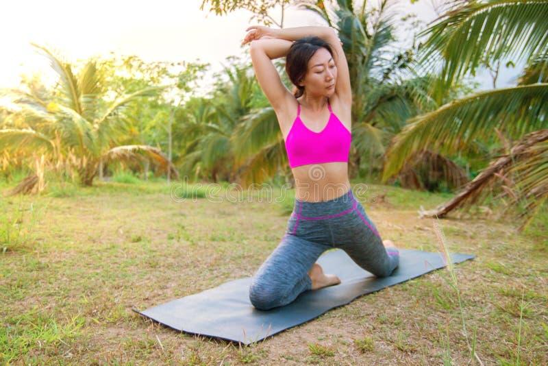 Jovem mulher que faz o exercício da ioga com a esteira da ioga na grama no por do sol imagens de stock royalty free