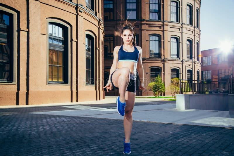Jovem mulher que faz o exercício do aquecimento antes de correr esticando seu pé na rua da cidade fotografia de stock royalty free