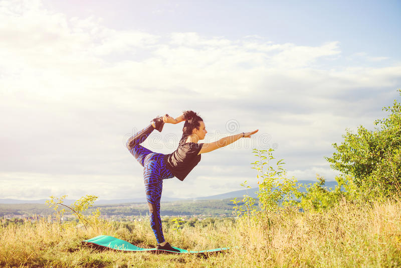 Jovem mulher que faz o exercício exterior, paisagem da ioga ou da aptidão da natureza no por do sol foto de stock