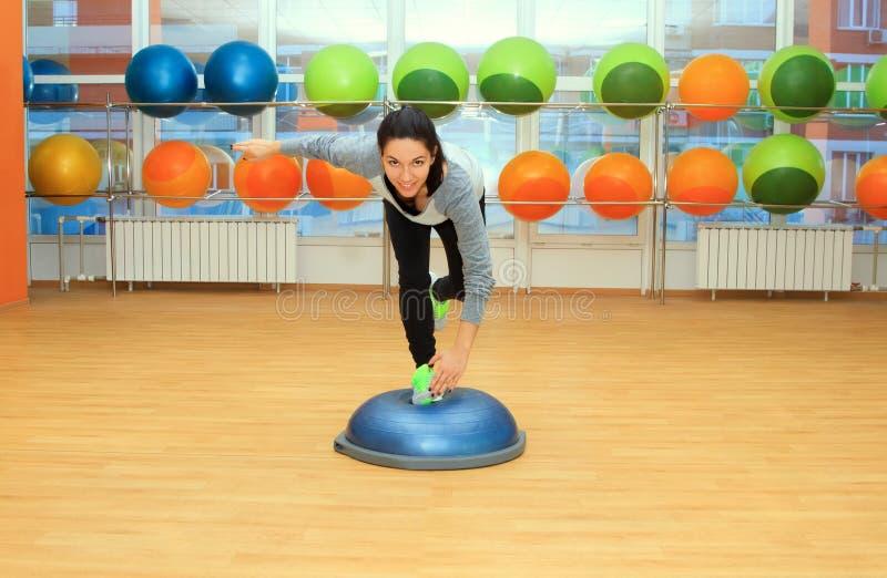 Jovem mulher que faz o exercício na bola do bosu foto de stock royalty free