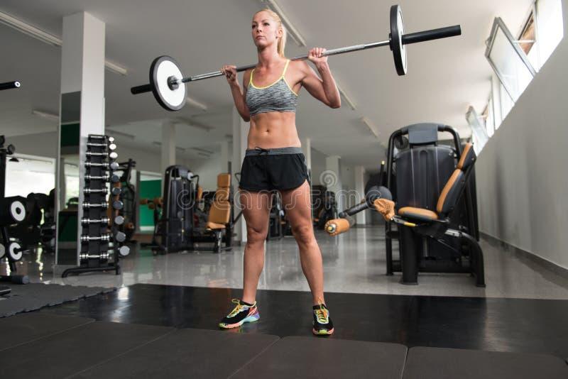 Jovem mulher que faz o exercício para os pés com Barbell fotografia de stock royalty free
