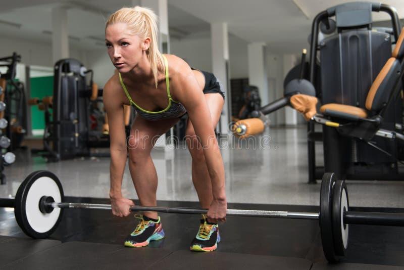 Jovem mulher que faz o exercício traseiro com Barbell foto de stock royalty free