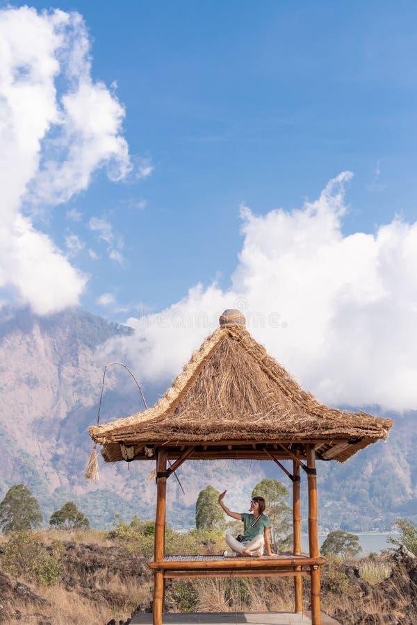 Jovem mulher que faz o selfie na natureza no miradouro no lago, ilha de Bali imagem de stock