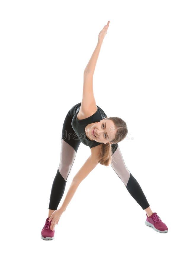 Jovem mulher que faz os exercícios dos esportes isolados no branco fotografia de stock