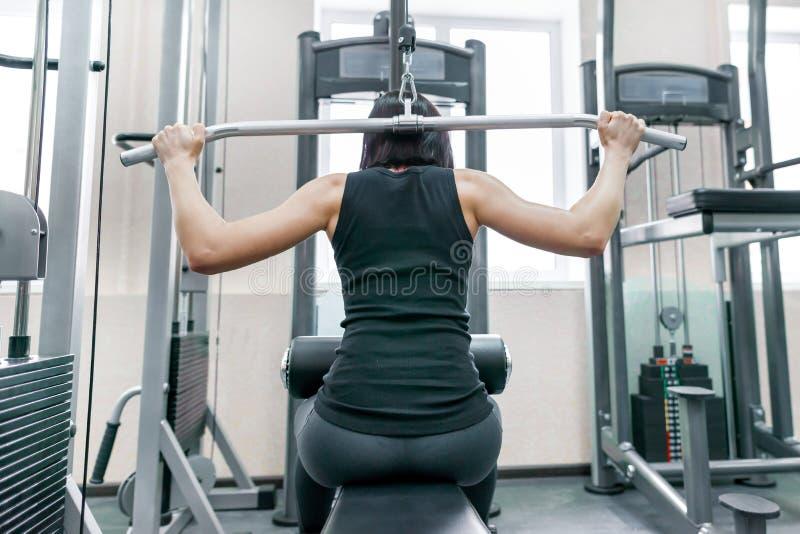 Jovem mulher que faz os exercícios para a parte traseira em uma máquina da aptidão no gym, vista da parte traseira Aptidão, espor fotos de stock