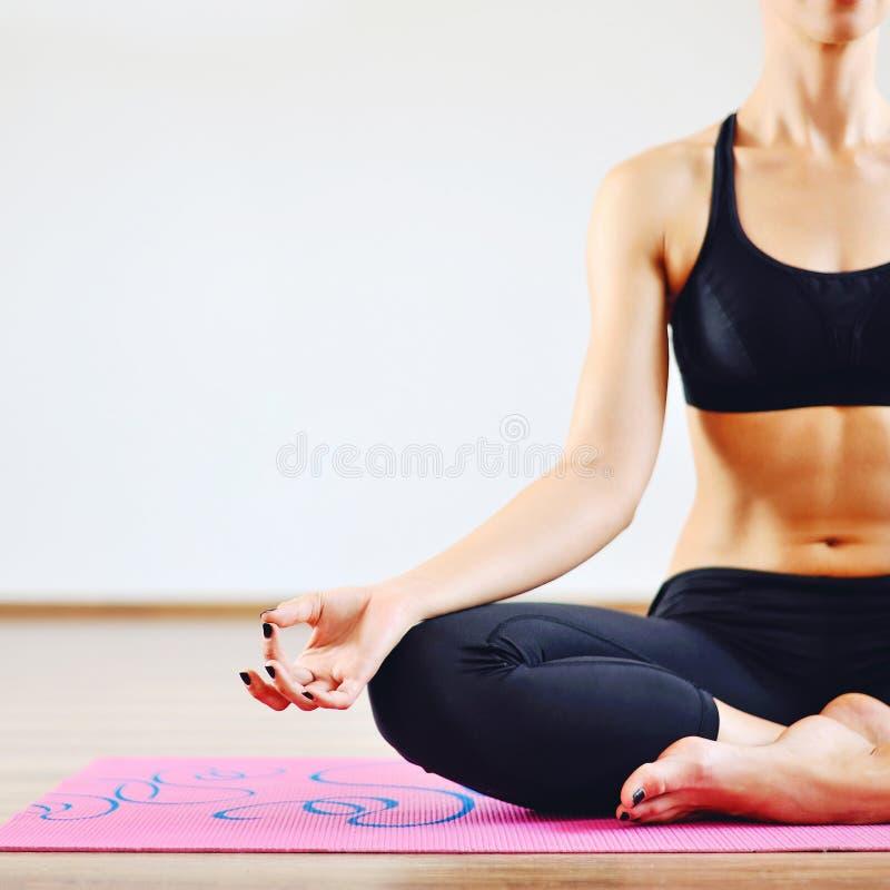 Jovem mulher que faz a parte do corpo da ioga dentro - imagem de stock royalty free