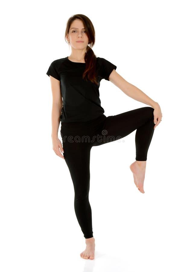 Jovem mulher que faz a pose da árvore de Vrksasana do asana da ioga fotos de stock