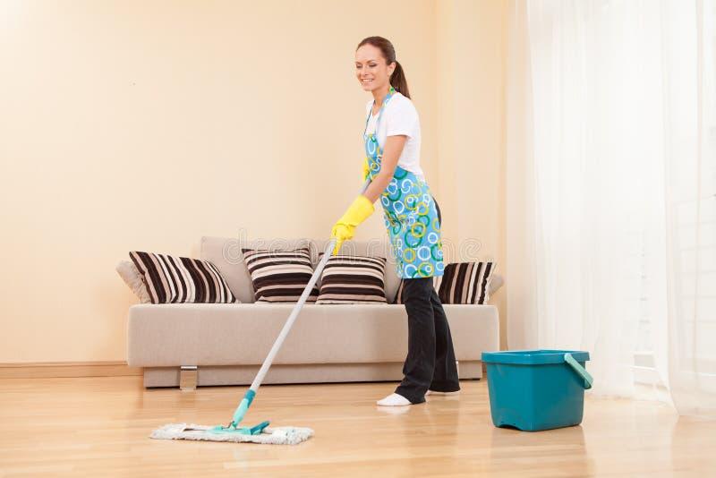 Jovem mulher que faz trabalhos domésticos e limpeza. fotografia de stock royalty free