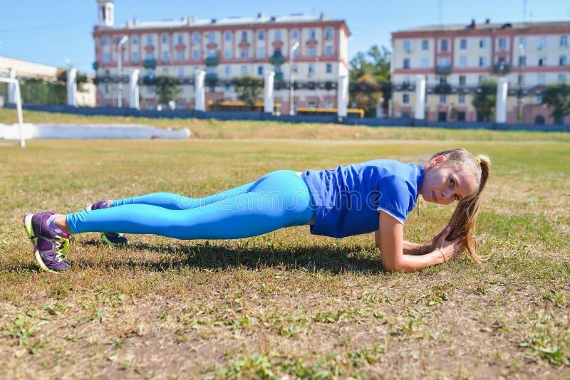 Jovem mulher que faz um exercício da prancha fora fotografia de stock royalty free