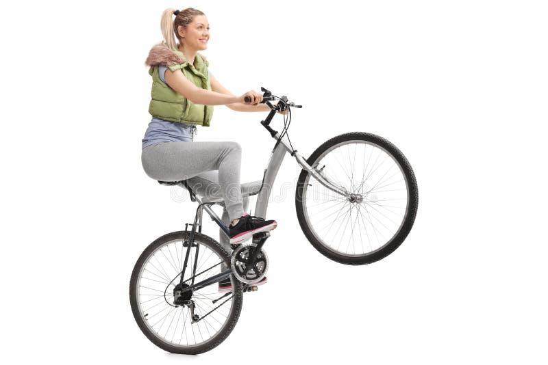 Jovem mulher que faz um wheelie em uma bicicleta fotos de stock royalty free