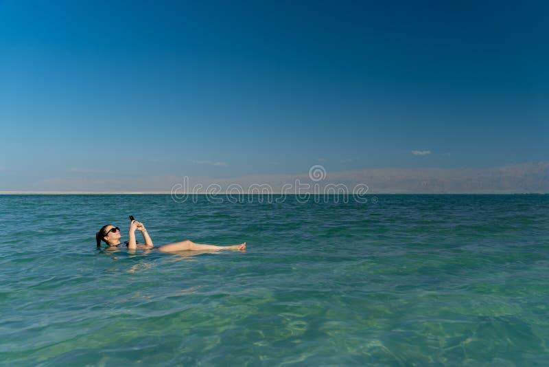 Jovem mulher que flutua na superf?cie da ?gua do Mar Morto e que usa seu smartphone foto de stock royalty free