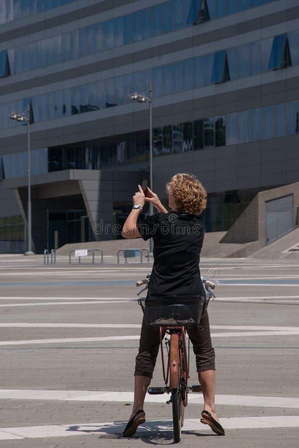 Jovem mulher que fotografa com um telefone celular foto de stock