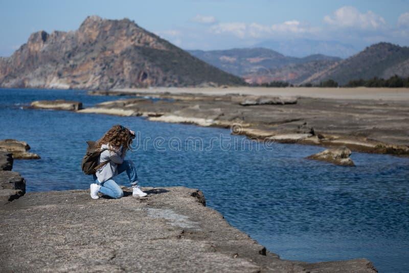 A jovem mulher que fotografa a rocha marcou a praia de Koru no Al de Gazipasha imagens de stock royalty free