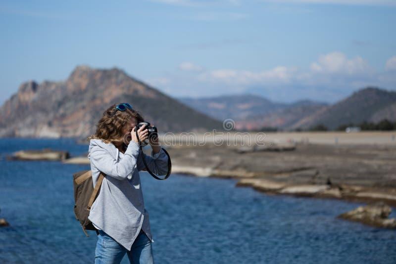 A jovem mulher que fotografa a rocha marcou a praia de Koru no Al de Gazipasha foto de stock royalty free