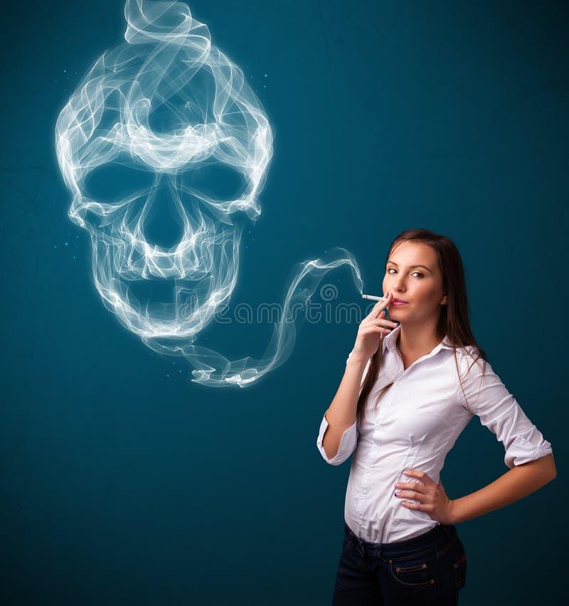 Jovem mulher que fuma o cigarro perigoso com fumo tóxico do crânio imagens de stock