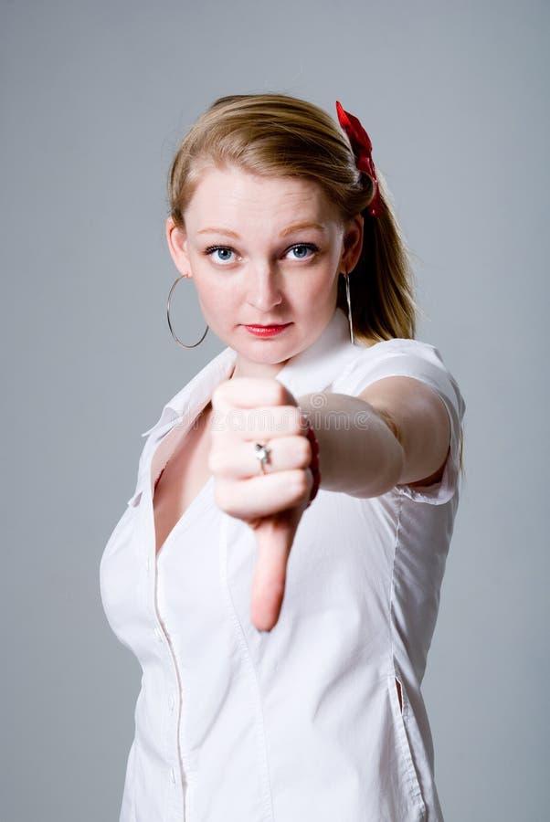 Jovem mulher que gesticula o polegar para baixo foto de stock royalty free