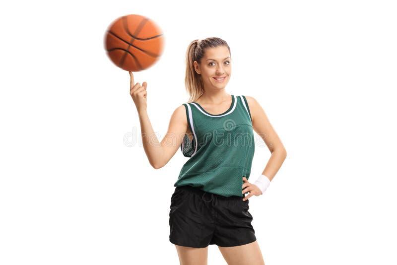 Jovem mulher que gira um basquetebol em seu dedo imagens de stock