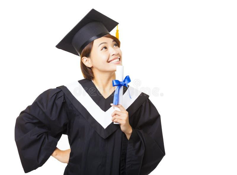 jovem mulher que gradua-se guardando o diploma e a vista foto de stock
