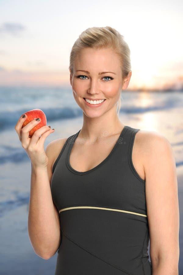 Jovem mulher que guarda Apple na praia foto de stock