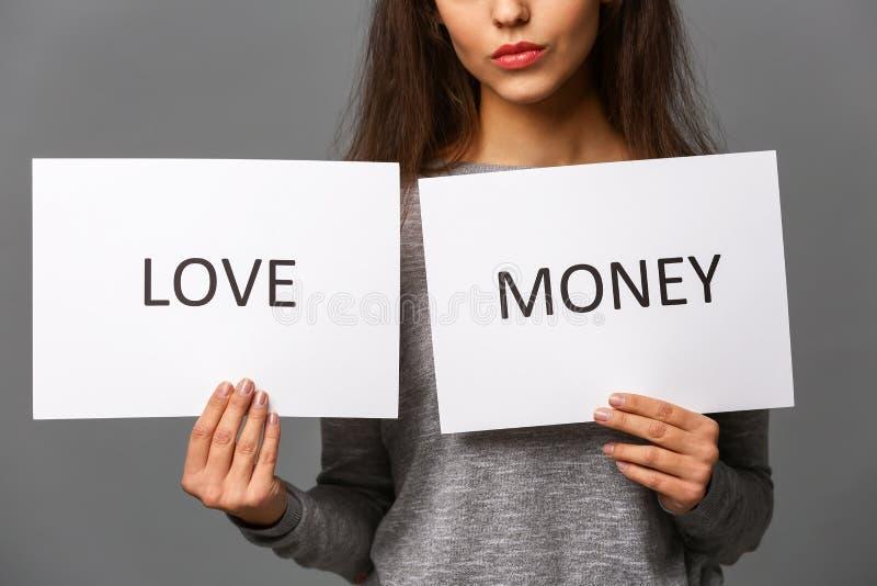 A jovem mulher que guarda as folhas de papel com palavras AMA e DINHEIRO no fundo cinzento Uni?o de conveni?ncia foto de stock royalty free
